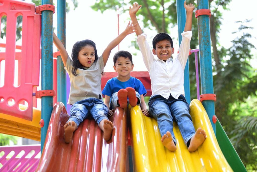 Three smiling siblings prepare to go down colorful slides at a local park.