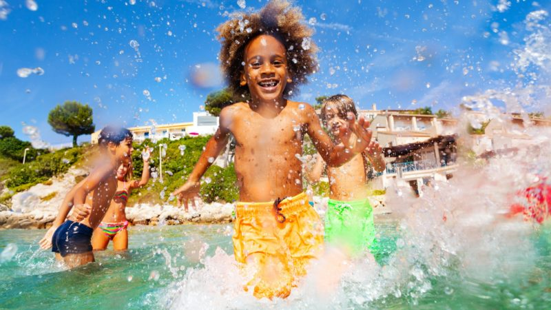 A young boy with a yellow swimsuit walks towards the camera while splashing water everywhere. His friends are playing in the background and the hotel airbnb is on a distant hillside.
