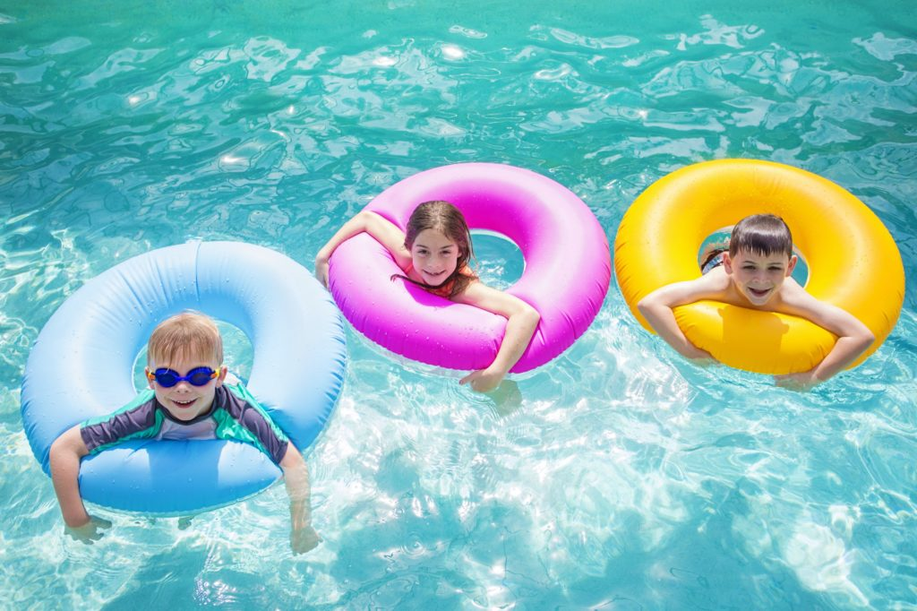 Three kids play in a swimming pool, hanging on colorful innertubes.