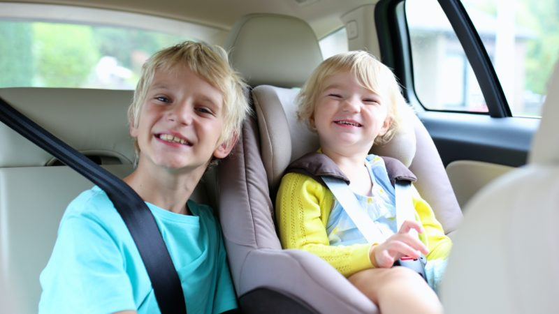 Smiling siblings sit in the backseat of a car. The younger of the two is wearing her seatbelt in a forward facing carseat. Her brother is smiling beside her.