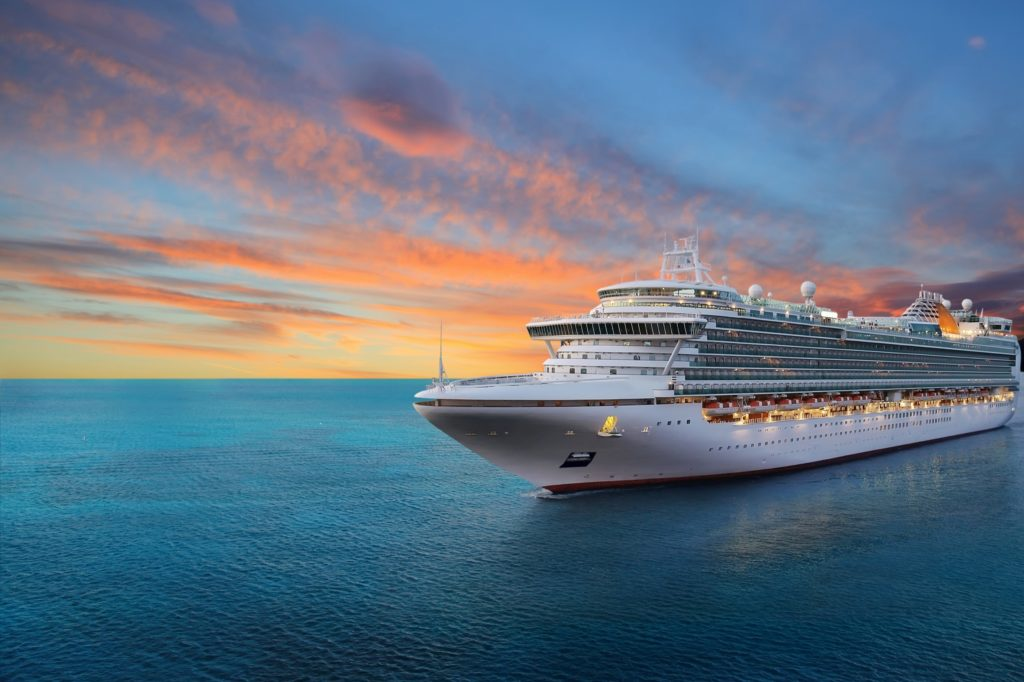 A white luxury cruise ship moves through an open blue ocean. The sunset has finished, leaving a colorful sky filled with orange and red clouds.