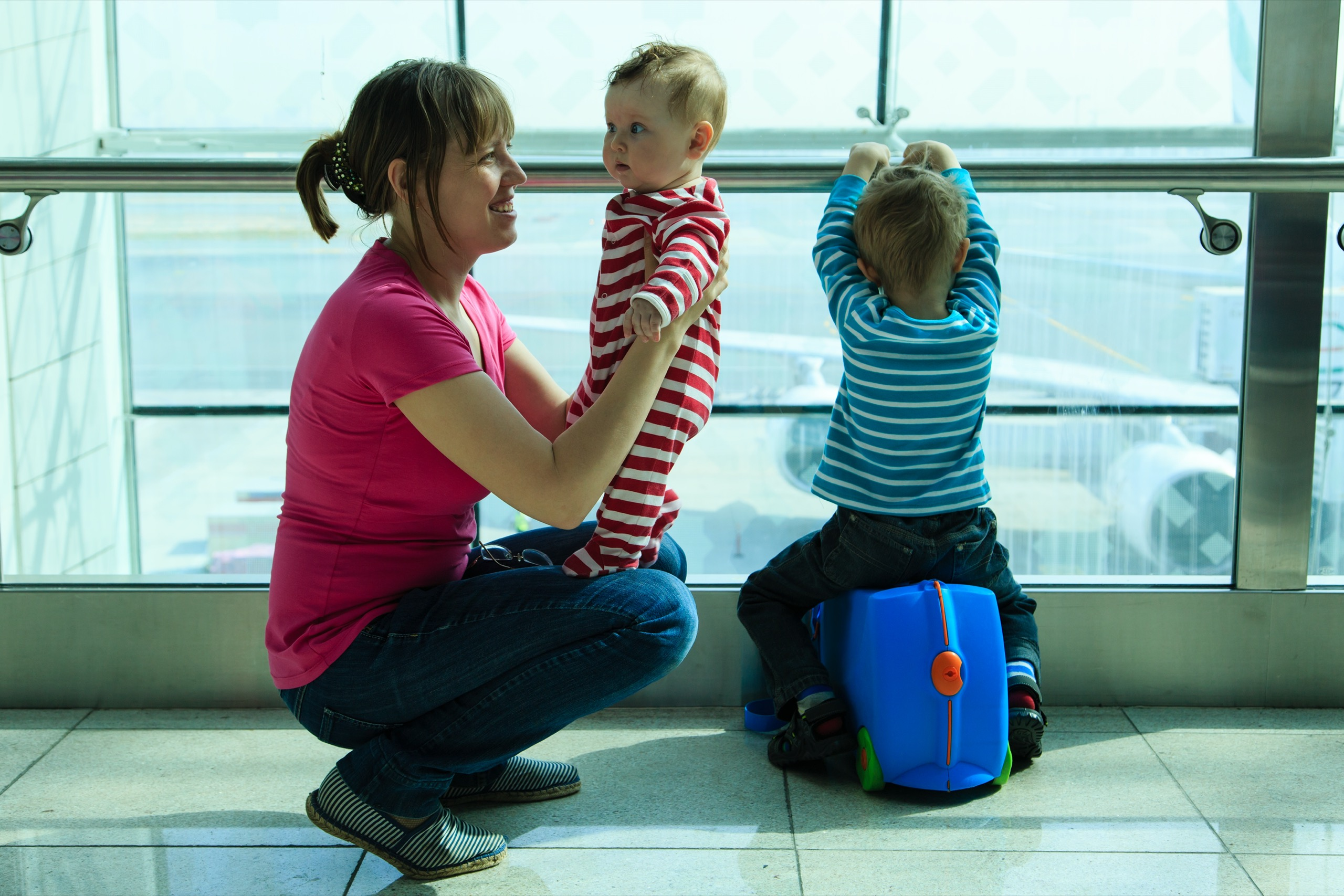 A mother holds a baby in both arms as her other child rests on a suitcase at an airport terminal. The mother is smiling and the older brother is looking out of the window at airplanes on the runway.