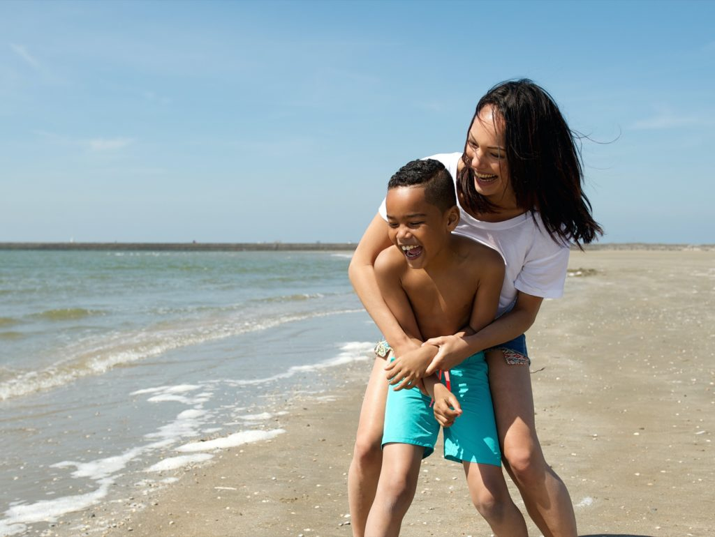 A mother holds her son from behind on a beach as they play and laugh. The boy is wearing a blue swimsuit.
