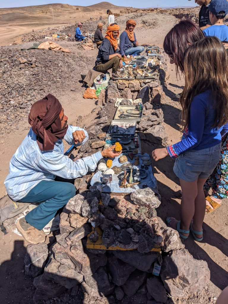 Moroccan merchants selling trinkets at a tourist site.