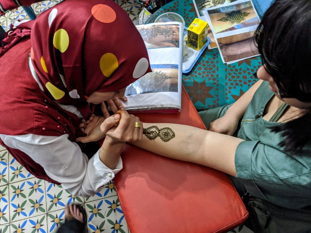 Moroccan woman gives a tourist a temporary henna tatoo.