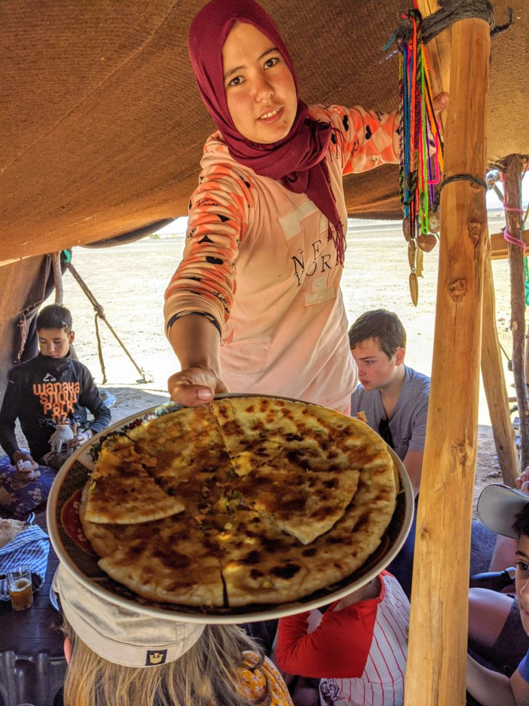 Nomadic woman offers bread.