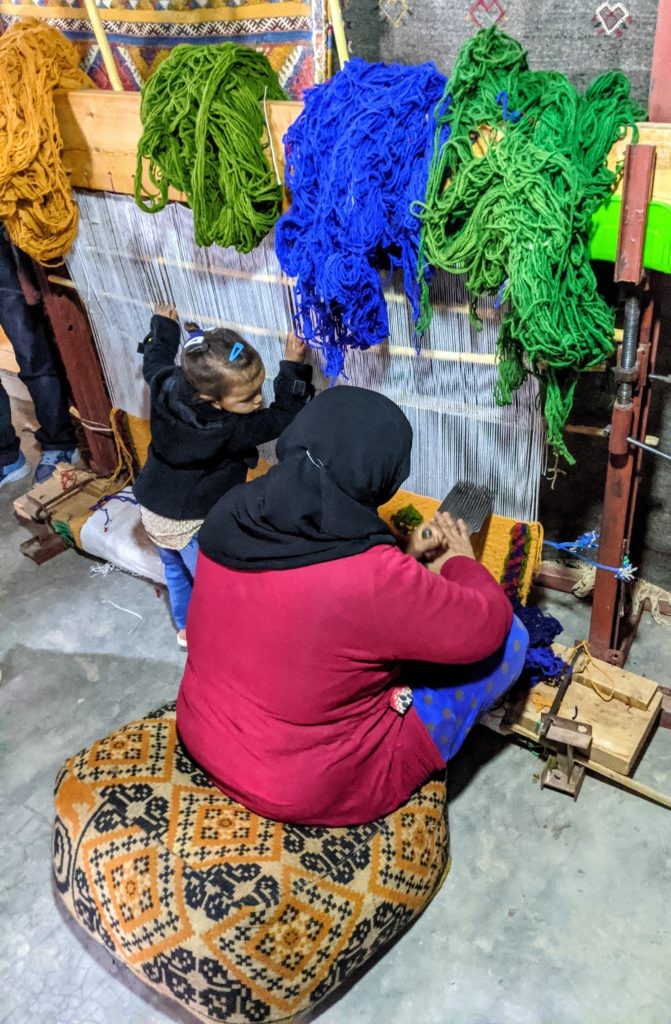 A woman and her daughter at a rug weaving coop in Morocco.