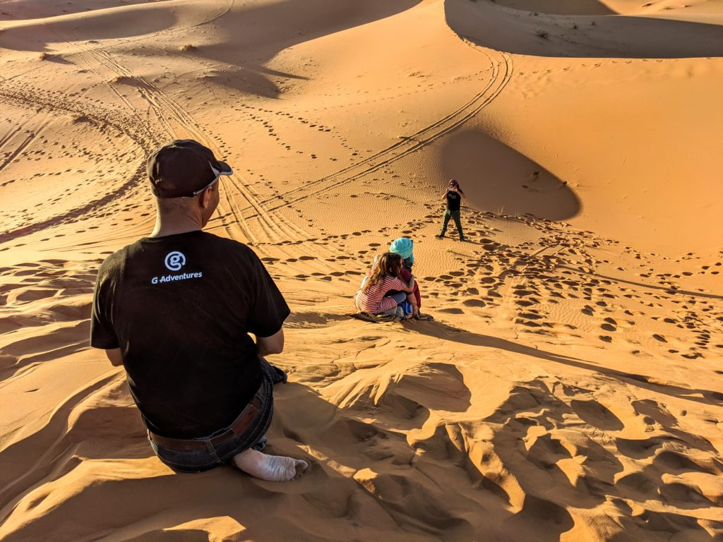 Kids sliding down the sand dunes in the Sahara Desert in Morocco.