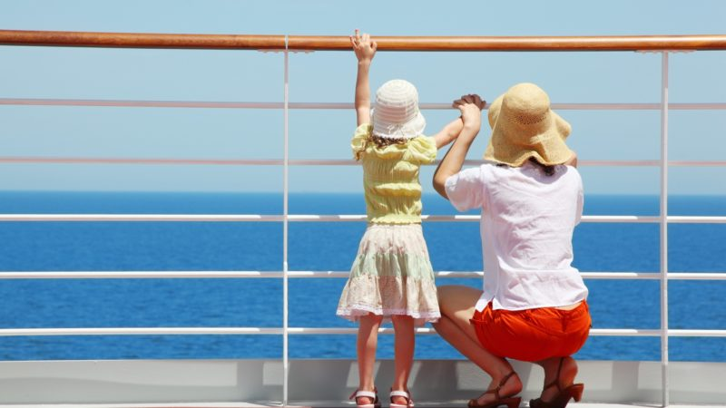 A mother and daughter look at the blue ocean off the deck of a cruise ship. The mother is holding the daughter's hand and crouching beside her. They are both wearing knit hats.