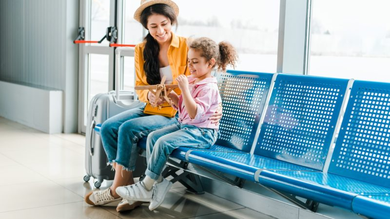 A mother sits on a bench at an airport with her daughter. They are playing with a wooden model airplane and smiling.