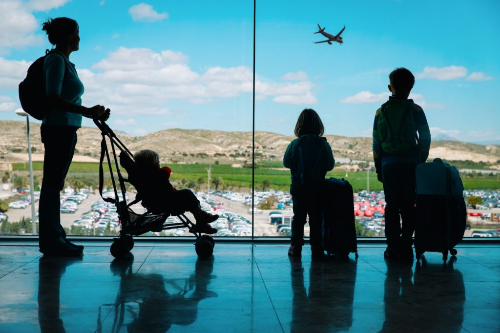 A mother and her three children watch out of the window at an airport of an airplane in flight. The mother is pushing a baby in a stroller and each of the other children have a piece of rolling luggage/suitcase.