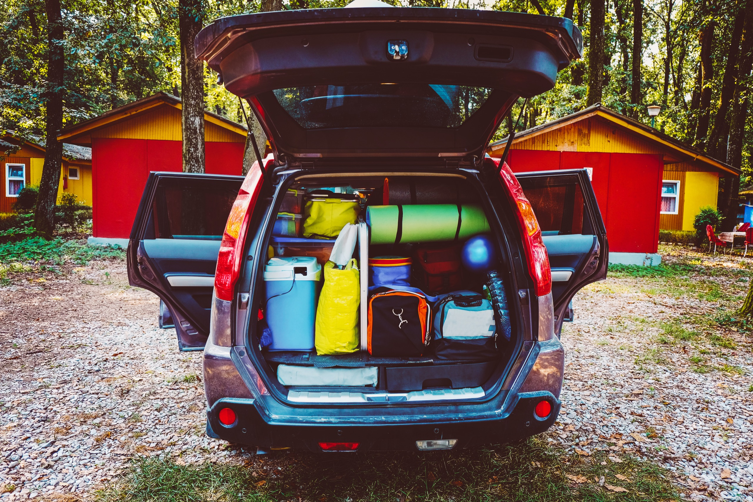 A sport utility vehicle/car is expertly loaded at a wooded campground. The suitcases, bags, and coolers are ready to be unloaded.
