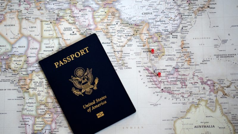 A United States passport is shown resting on a colorful world map. Travel documents like a passport are essential for international travel.