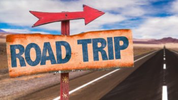 A close-up of a weathered sign displaying the words Road Trip with a desert highway racing into the mountain filled distance