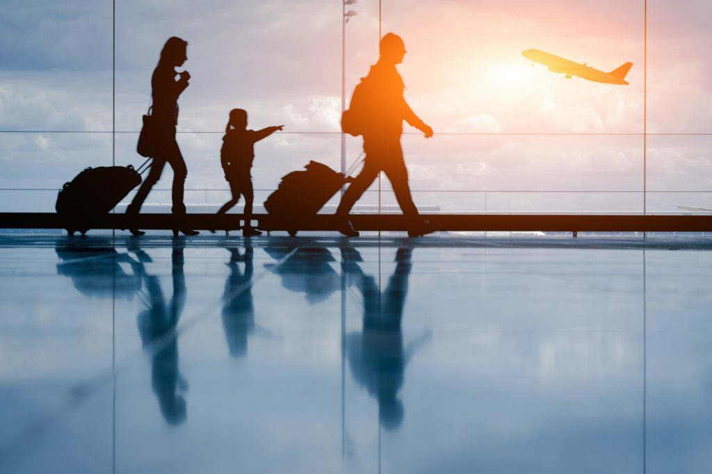 A family walks in an airport terminal near a window with an airplane taking off in the background. The sunset view shows them pulling their rolling luggage while a young girl points towards the airplane.