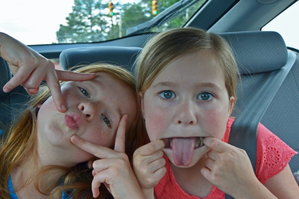 Two silly girls make funny faces at the camera as they sit in the backseat of a car The two friends are making the best of the road trip.