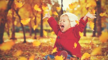 A thrilled young girl throws leaves in an autumn setting. She's wearing a hat and red jacket and has her mouth wide open from laughing