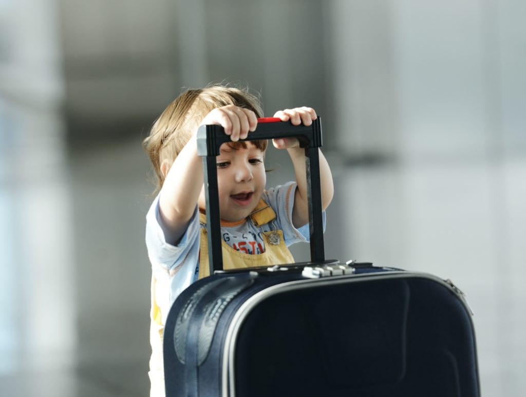 A toddler holds the handle of a suitcase in an airport.