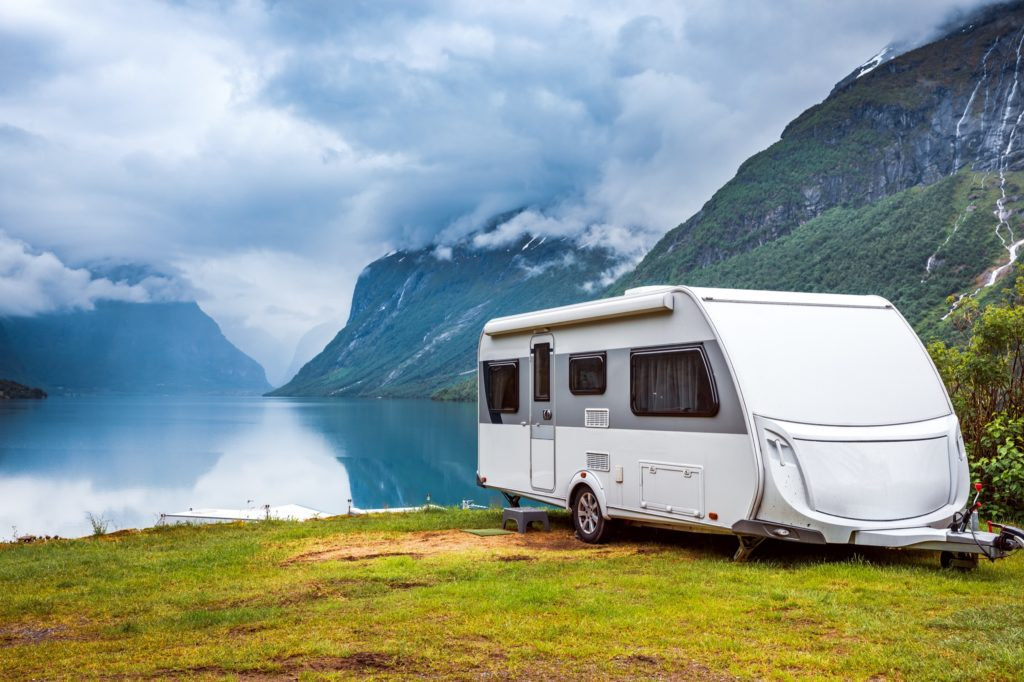 A camper trailer is set up near a peaceful fjord. The tree filled mountains line both sides of the photograph.