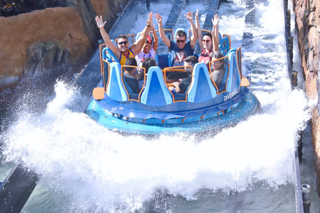 Guests are smiling and laughing excitedly while riding a white water rafting craft at a theme park/amusement park in Orlando, Florida.