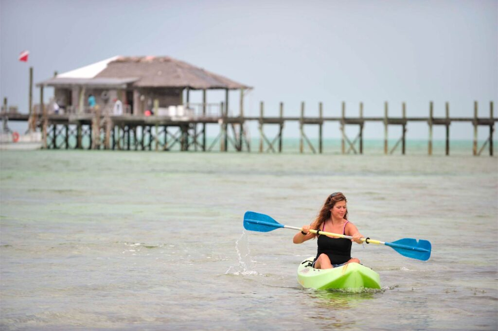A woman kayaking from Small Hope Bay Lodge, an all inclusive resort