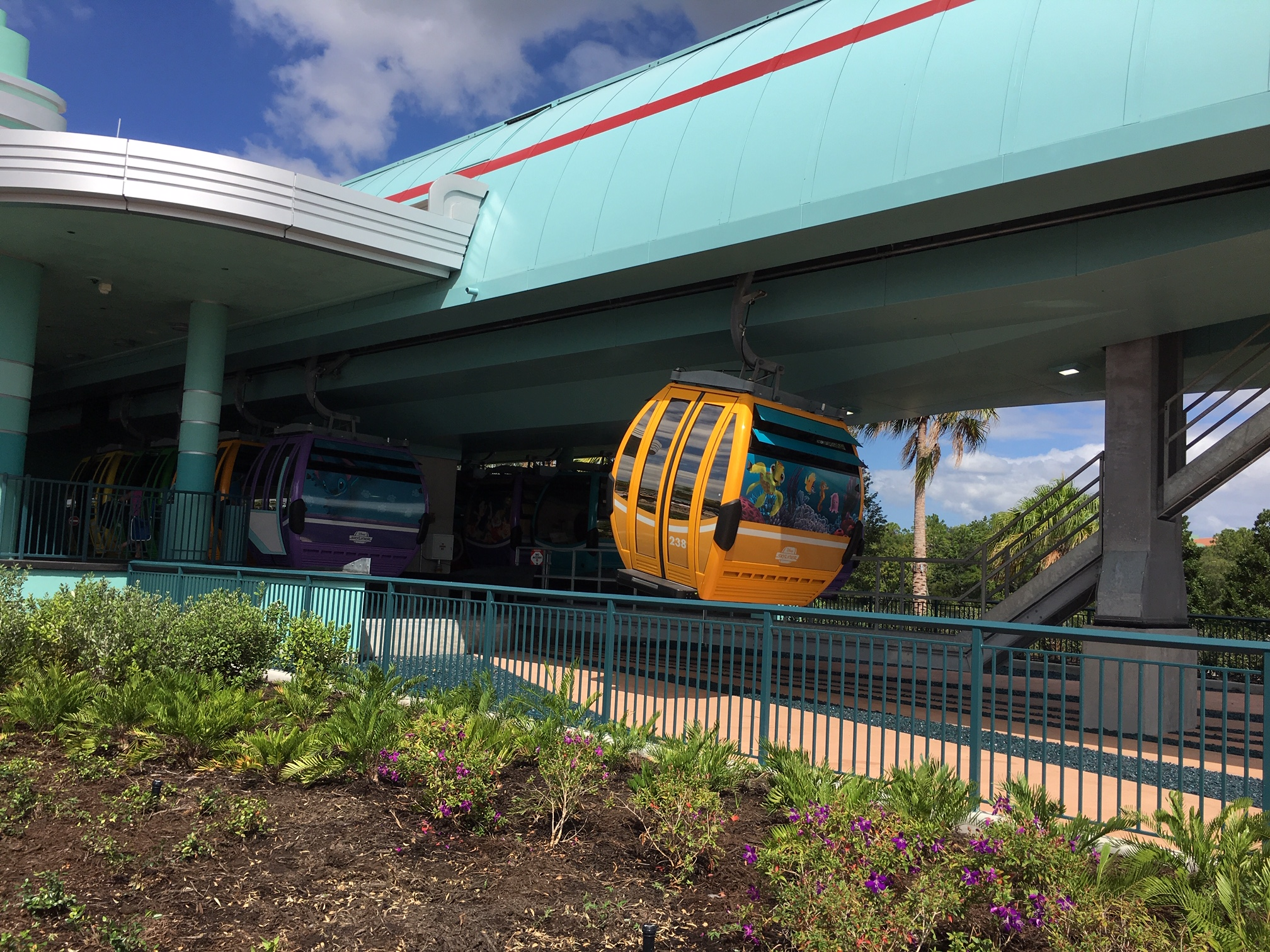 yellow Disney Skyliner gondola leaving Disney's Hollywood Studios Skyliner station