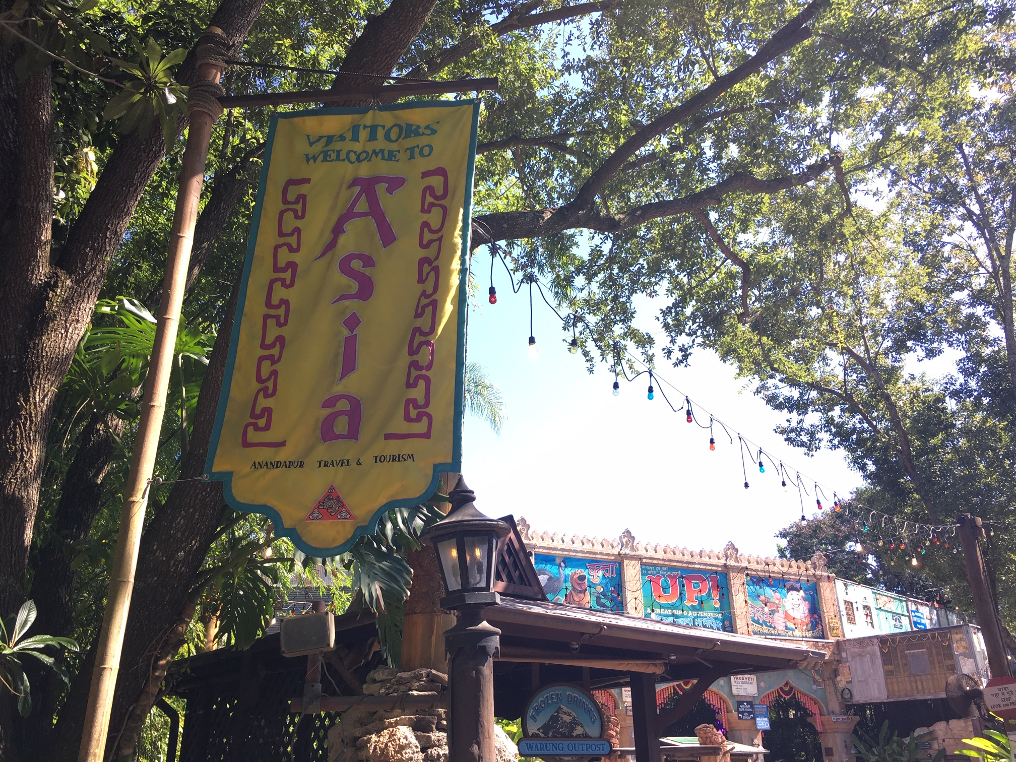 Located near Expedition Everest Disney World thrill ride - View of Disney's Animal Kingdom UP! Bird Show with Yellow Asia flag in the foreground