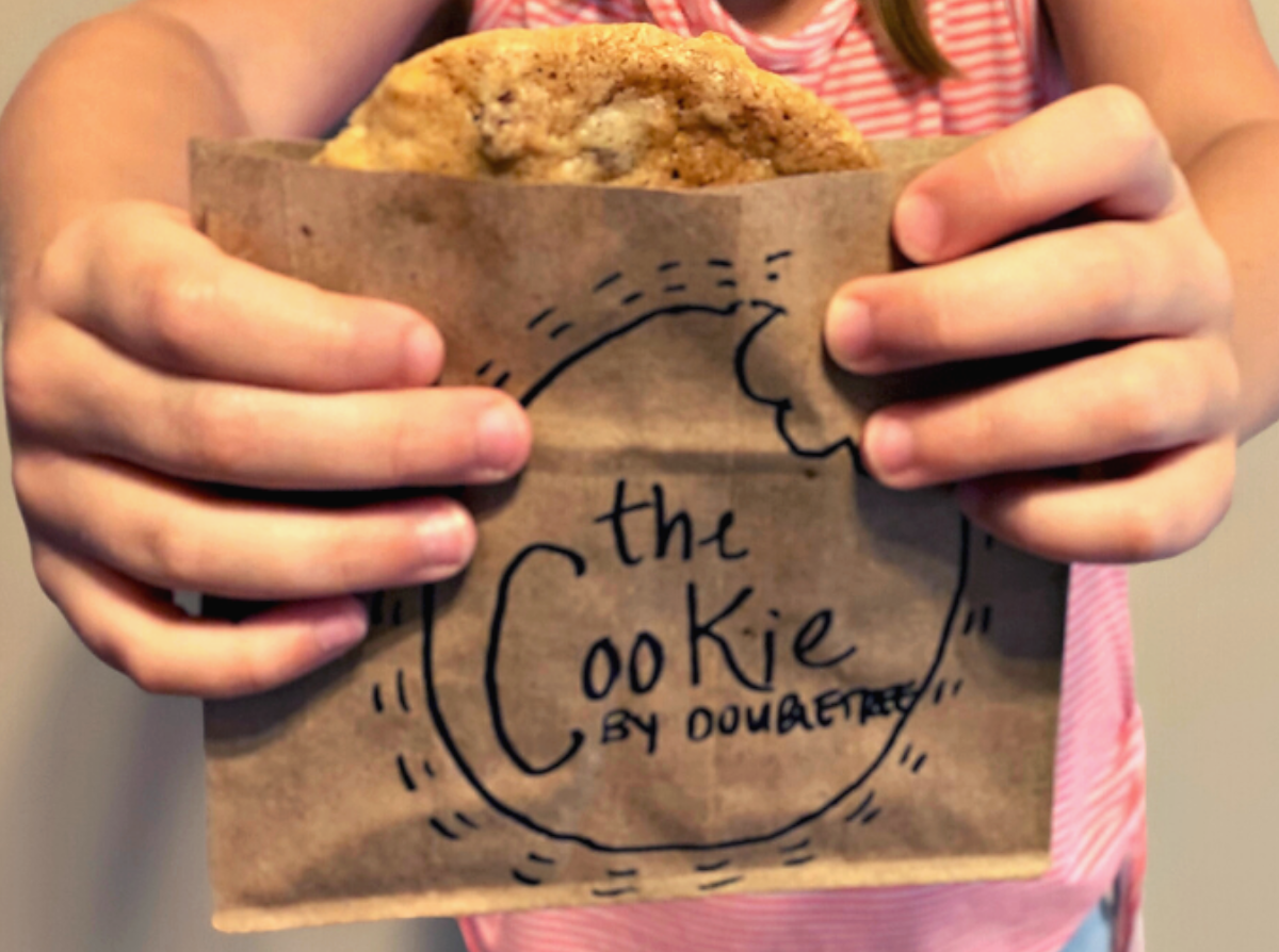 Childs hands holding paper bag with doubletree chocolate chip cookie in it