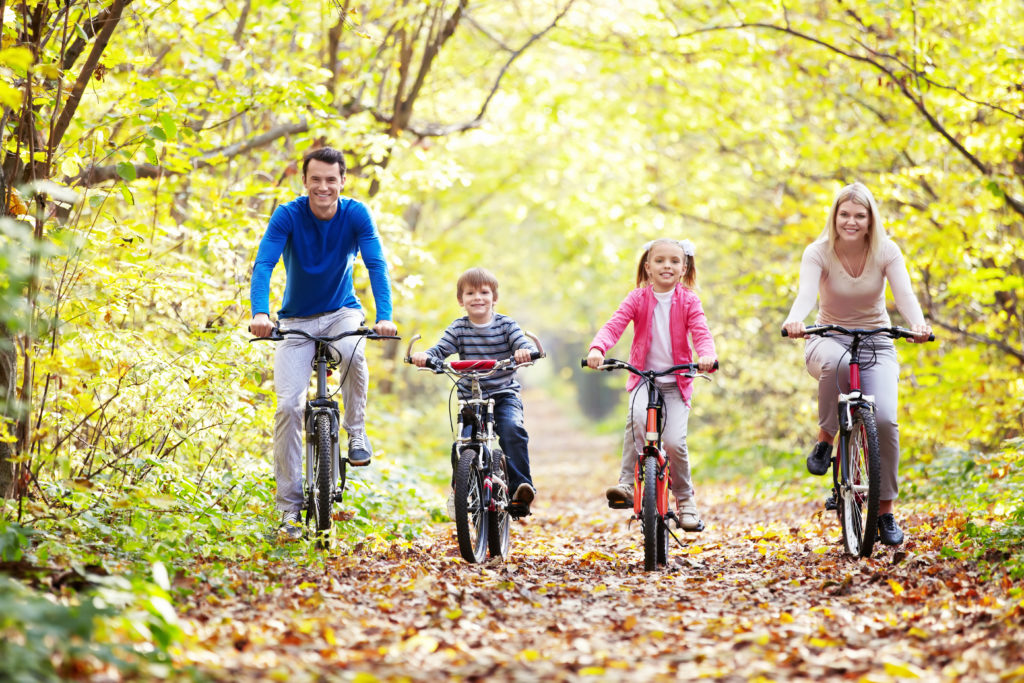 Mom, Dad, two kids biking on a wooded trail in the fall.