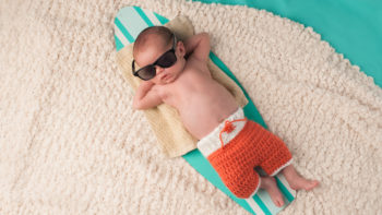 Cut baby boy sleeping on tiny surfboard