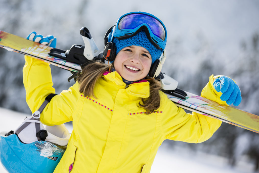 girl in a yellow jacket carrying skis