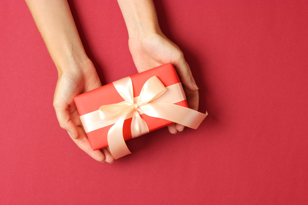 hands holding a red wrapped Christmas gift