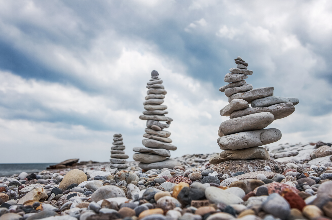 stones stacked up on lakefront cloudy day