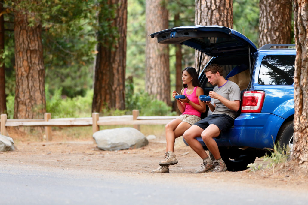 Couple on car road trip travel in eating in forest having lunch break outdoors