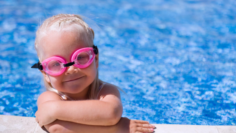 Toddler girl wearing swim goggles in a swimming pool