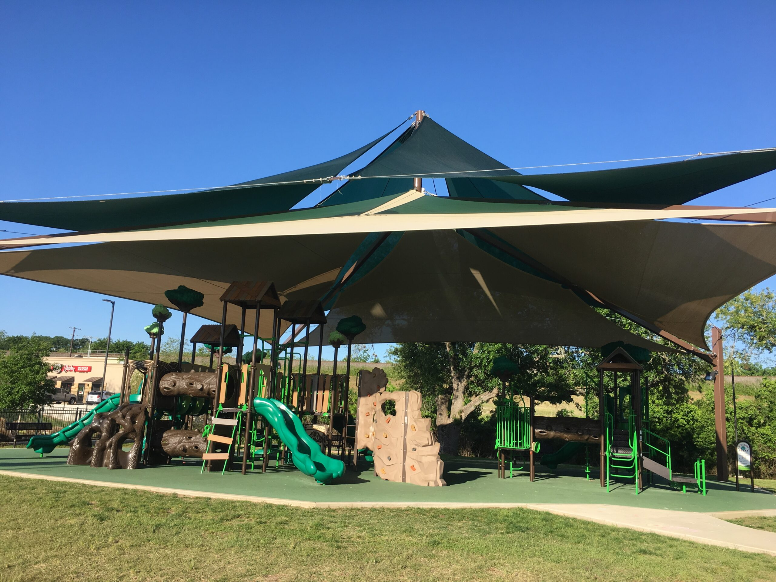 shaded playground with green slide and tan rock climbing wall