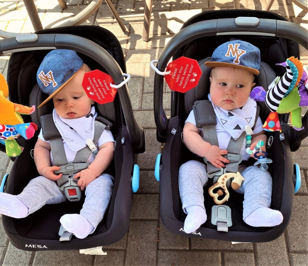 Traveling with babies: two twin boys in their infant car seats wearing baseball hats