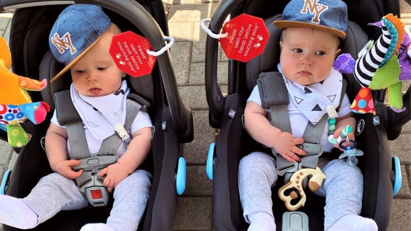 two twin boys in their infant car seats wearing baseball hats