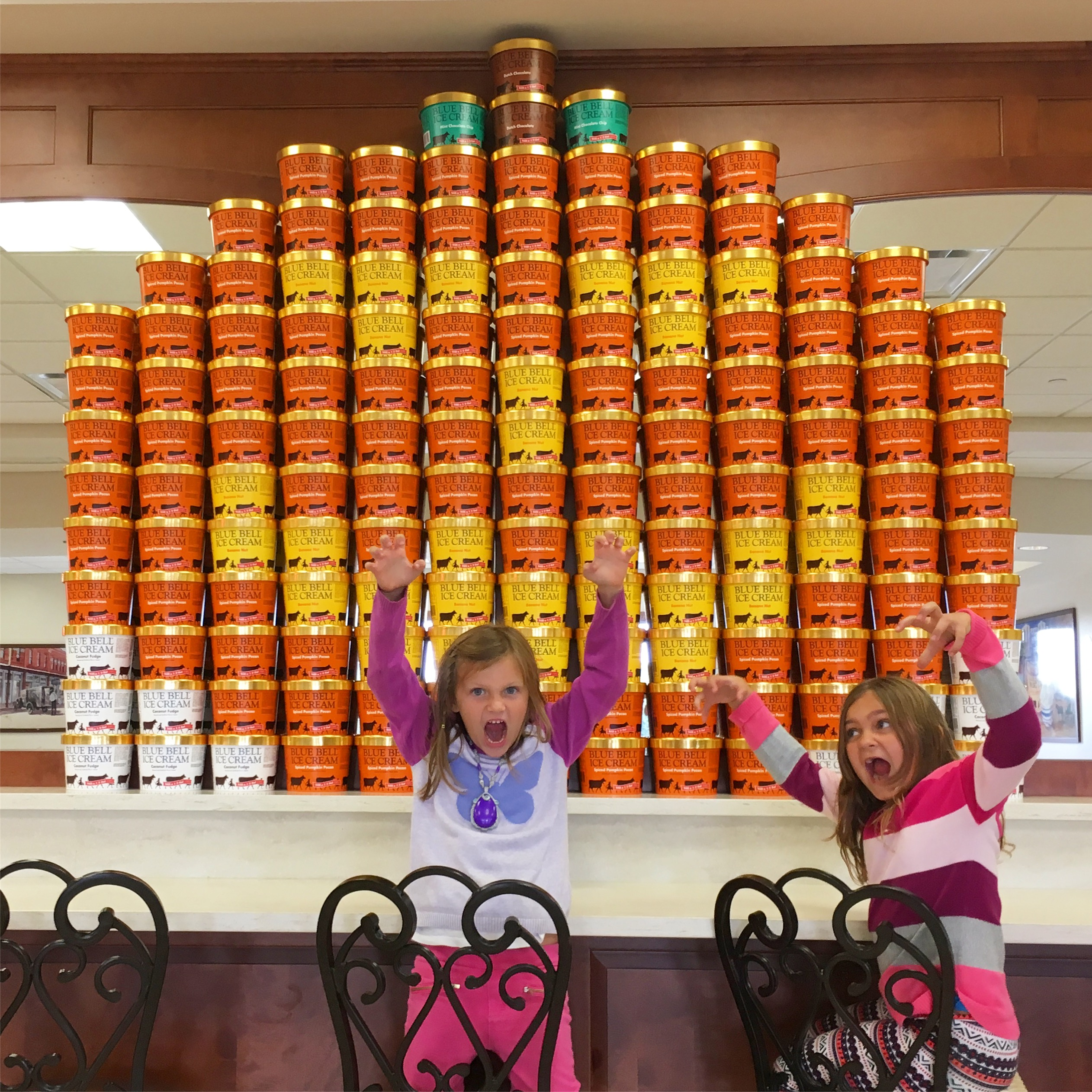 two blonde girls wearing bright sweaters and making faces in front of a display of ice cream half gallons that form a jack o'lantern