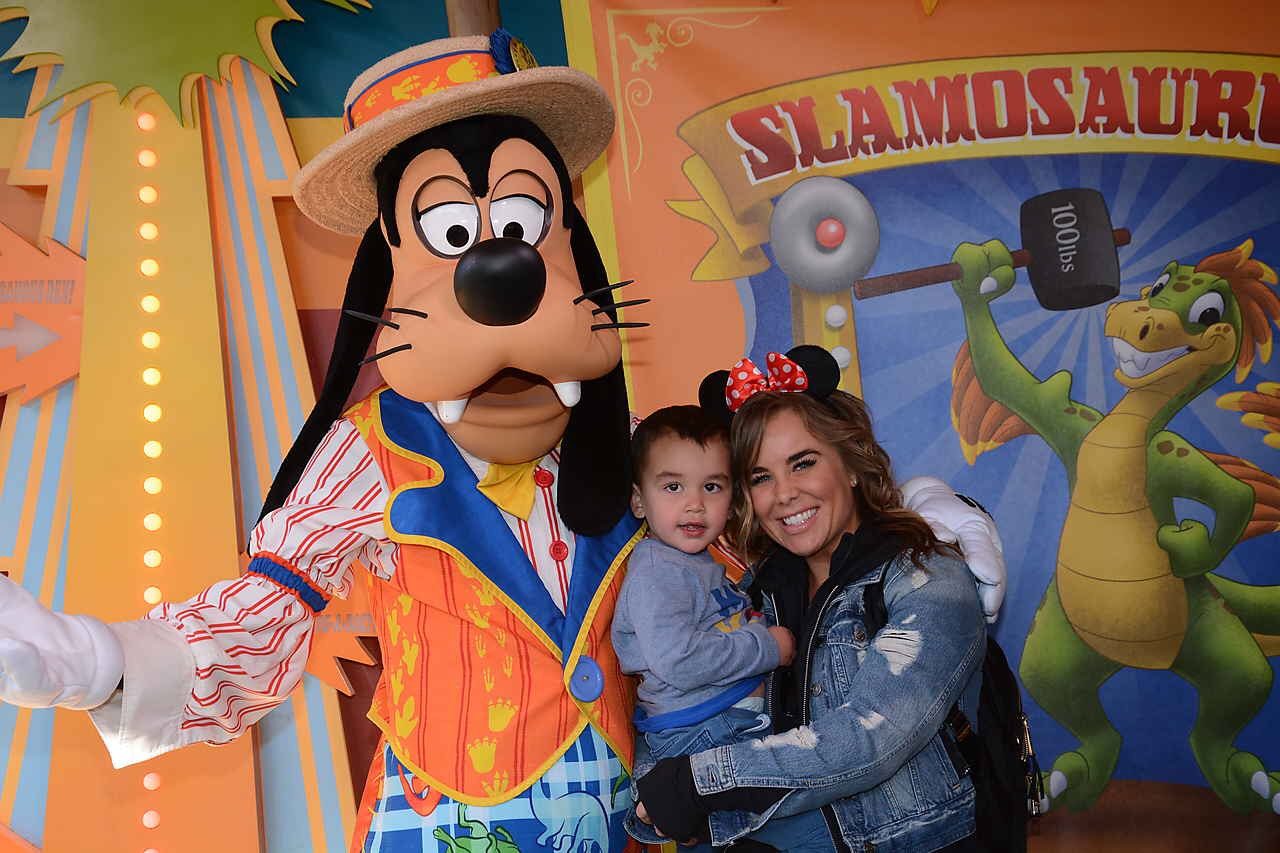 """Disney glossary, this photo depicts a """"Disney character,"""" played by a """"cast member"""" posing with """"guests"""" for a """"Photopass"""" picture."""
