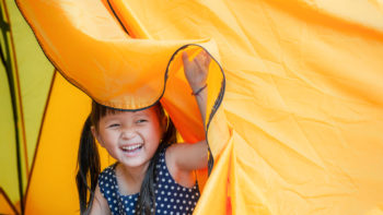 little girl peeking out of a tent camping