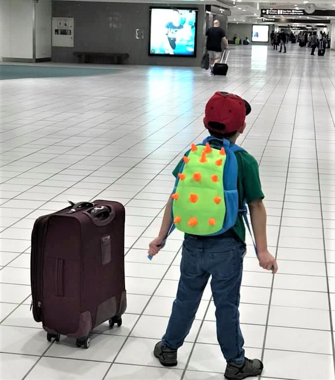 kid wearing dinosaur backpack standing next to luggage at airport