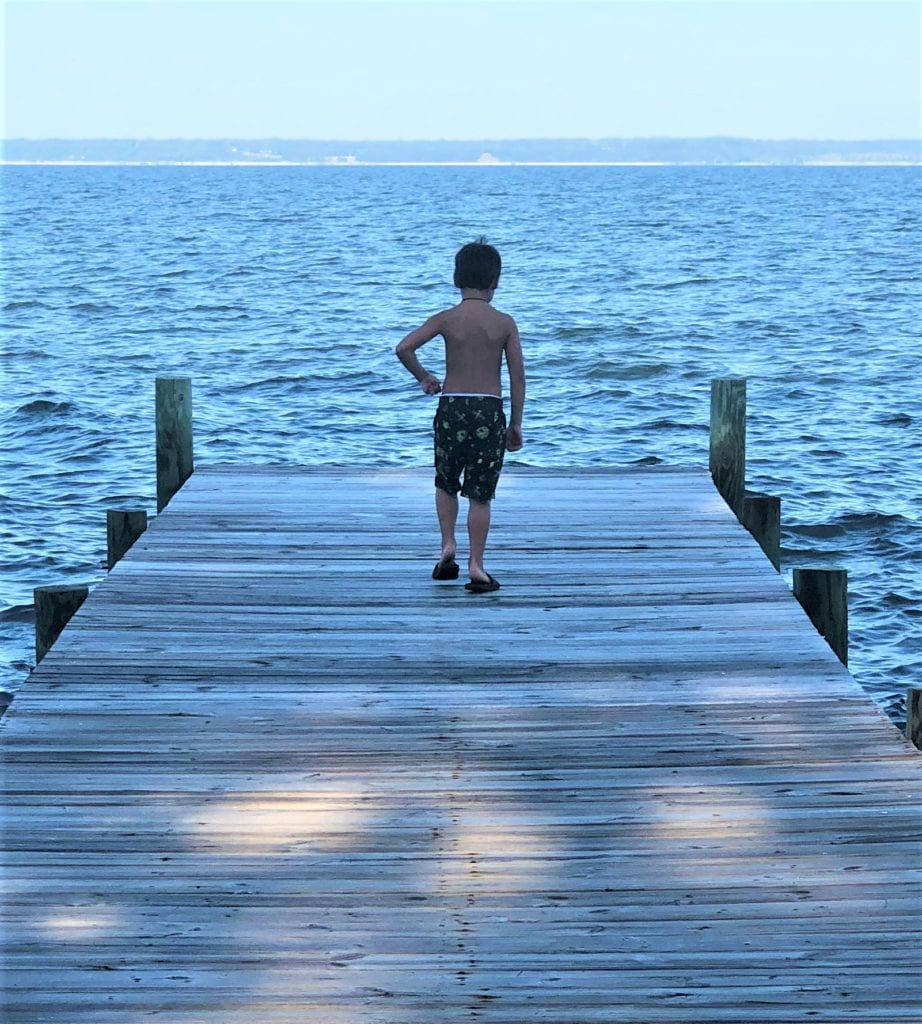 Boy on a dock at a lake