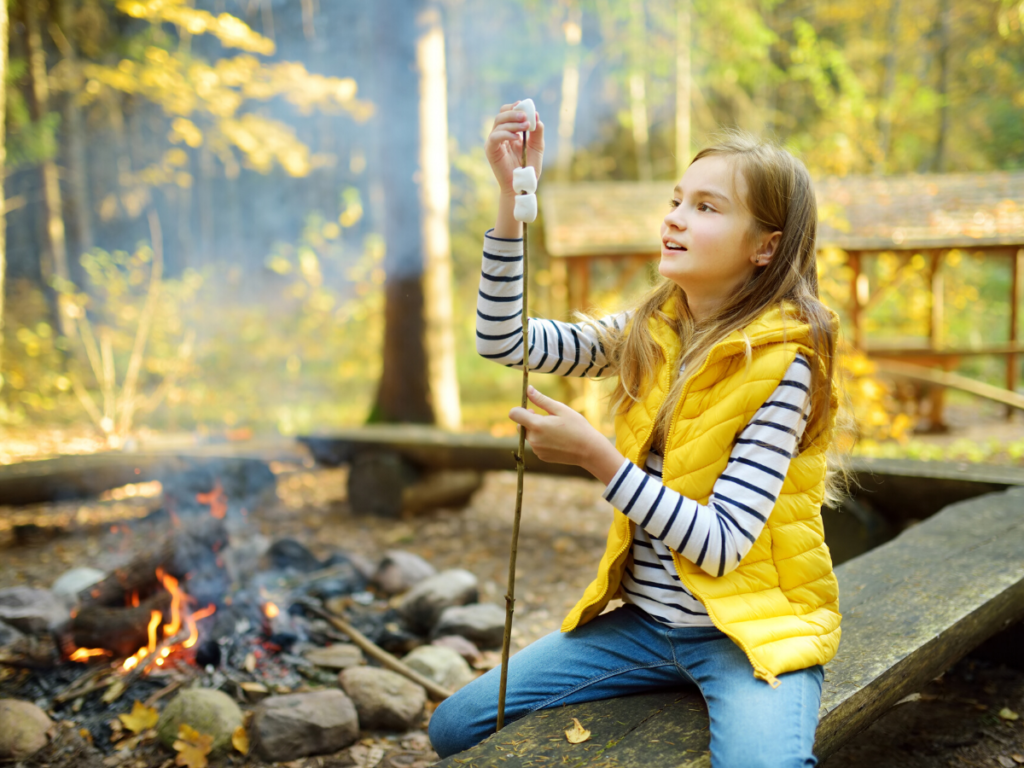 girl in yellow vest and striped shirt about to roast a marshmallow over a campfire