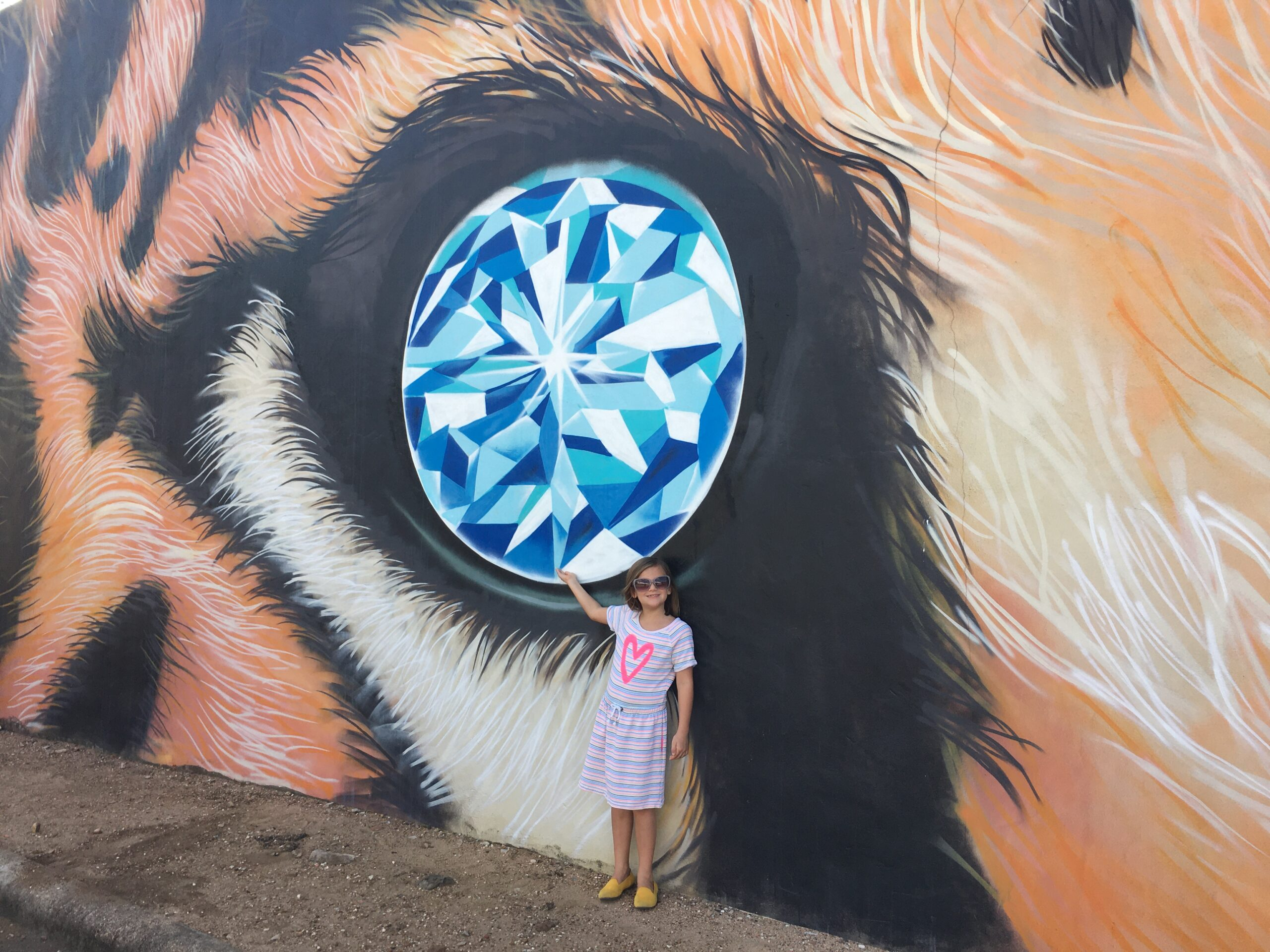 blonde girl wearing sunglasses and a dress in front a of large mural that depicts a tigers face and a diamond eye