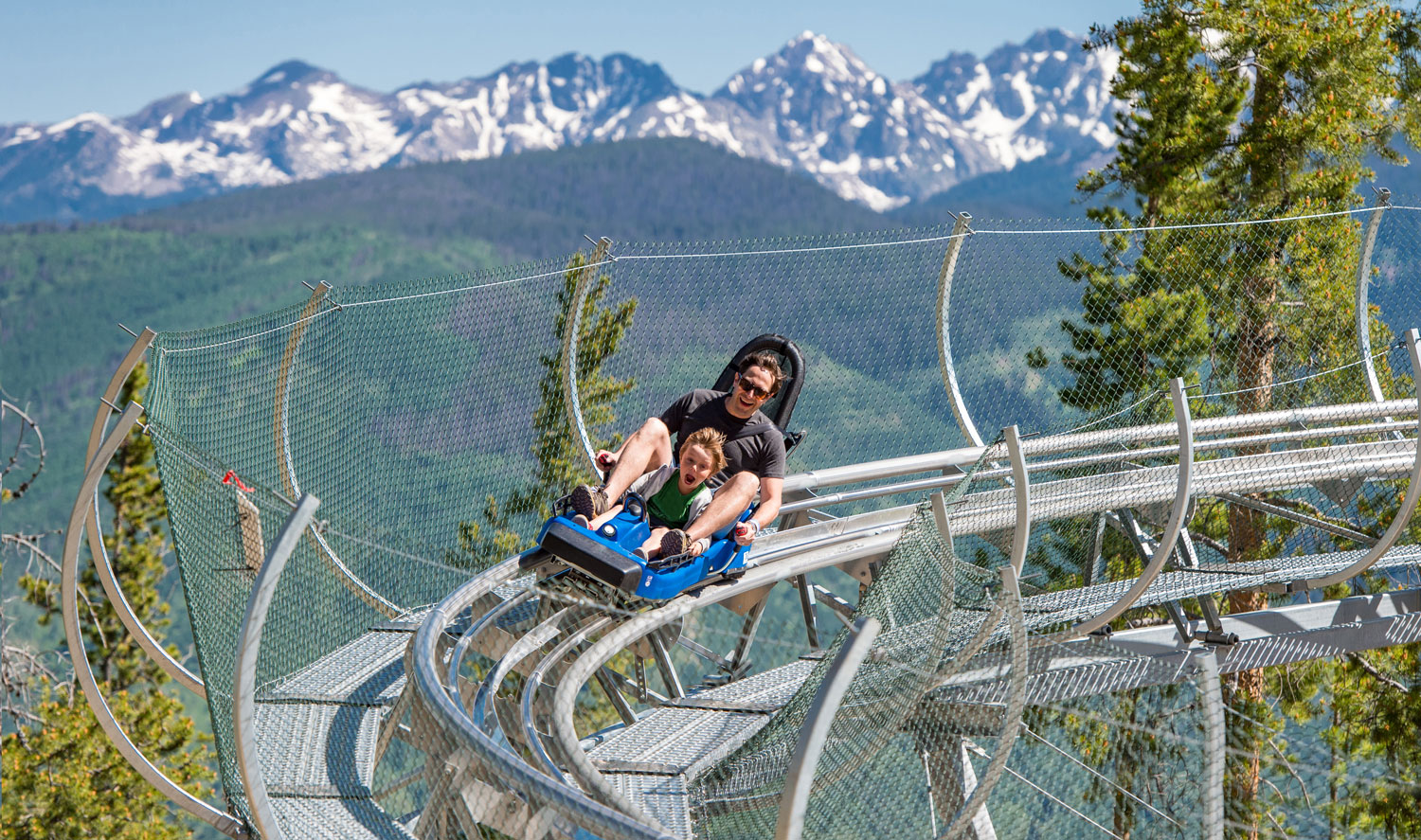 Dad and boy going down the alpine coaster in Vail