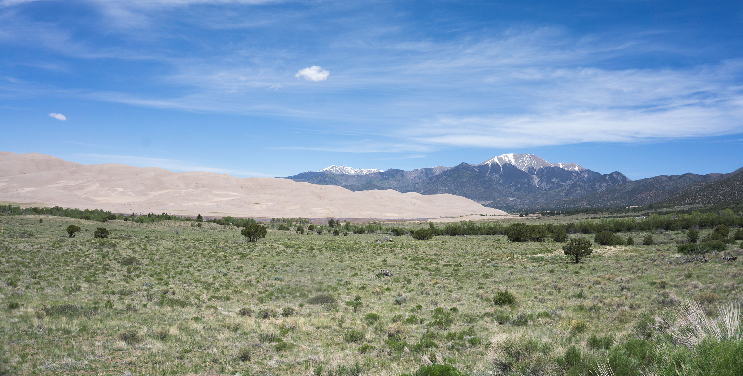 sand dunes in front of snow capped mountain peak in Great Sand Dunes National Park