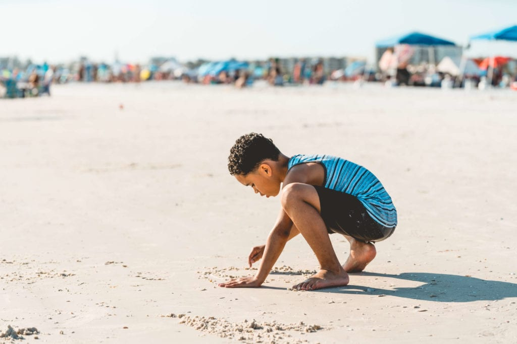 Boy playing in the sand in sarasota, florida