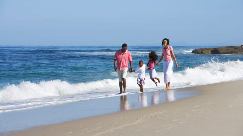 Family playing on a beach on a socially distant vacation.