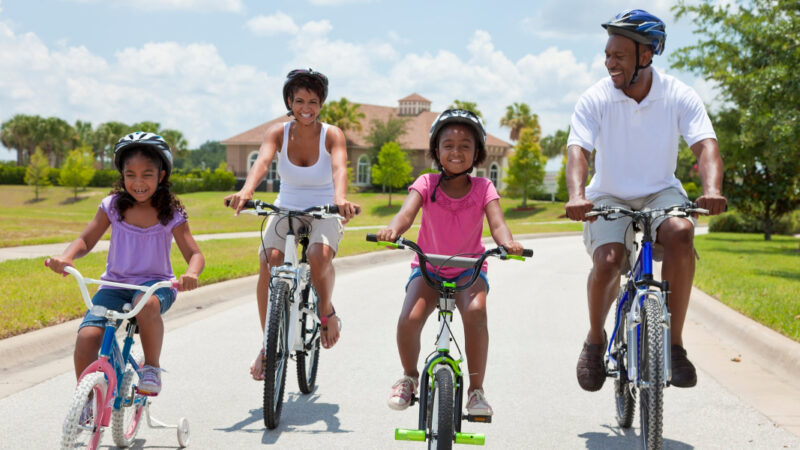 Riding bikes is a great activity for bonding when Black family travel together.
